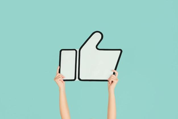 Mani che tengono il segno di like su sfondo blu