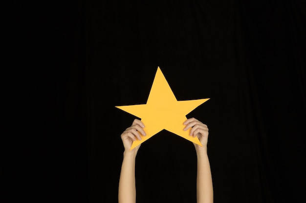 Hands holding the sign of star on black background