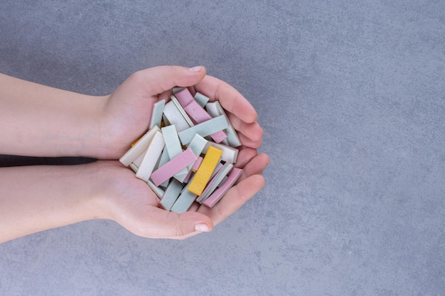Hands holding a small heap of bubblegum sticks on marble surface