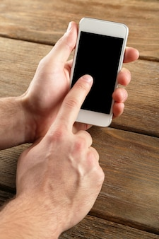 나무 테이블 배경에 스마트 휴대 전화를 들고 손