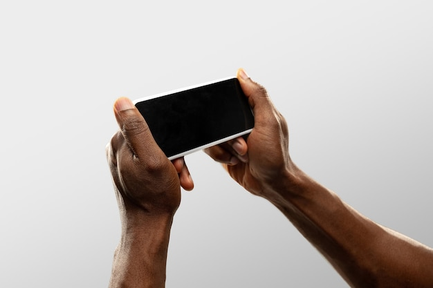 Hands holding smartphone, copyspace for ad. white background