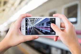 Hands holding smartphone on platform near train