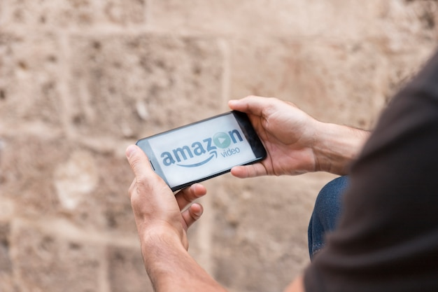 Hands holding smartphone showing amazon prime video app