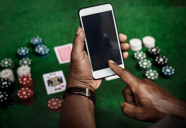 Hands holding smartphone while playing poker
