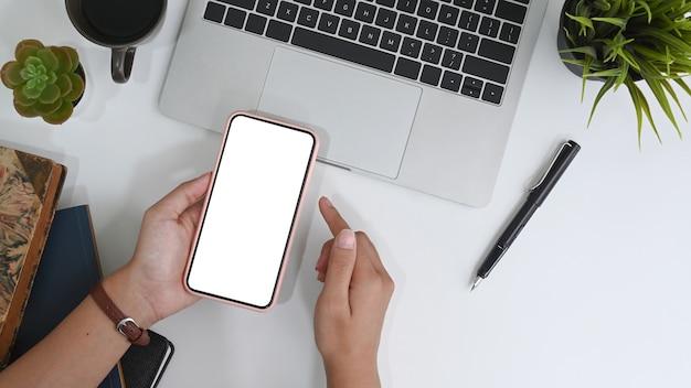 사무실 작업 공간에 빈 화면이 있는 스마트폰을 들고 있는 손, 상위 뷰 샷.