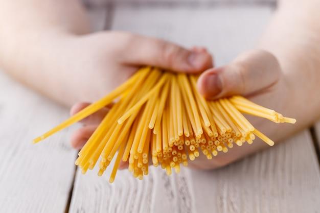 Руки держат спагетти на кухне