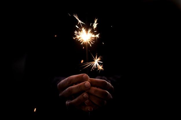 線香花火の光を持っている手。新年とクリスマスのお祝い