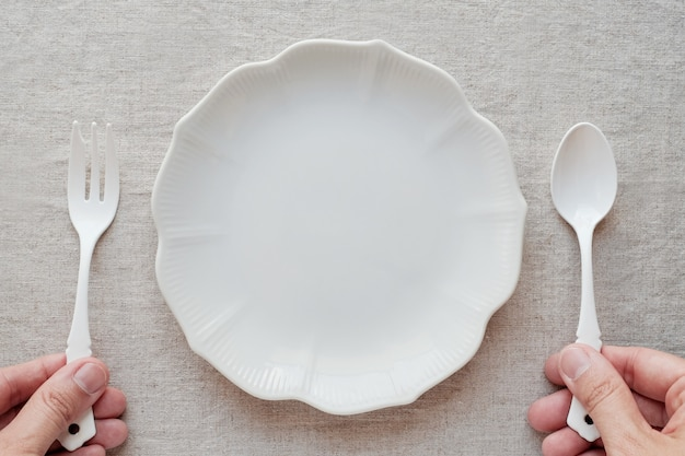 Hands holding spoon and fork with empty plate