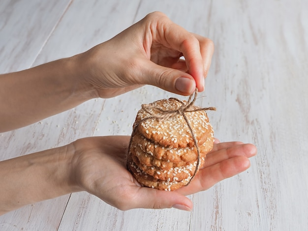 Hands holding a stack of fresh sesame cookies