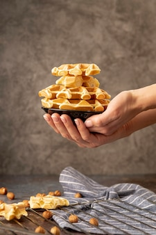 Hands holding stack of waffles on plate