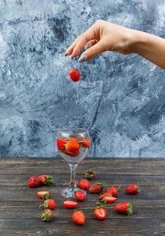 Mani che tengono le fragole sulla tavola di legno