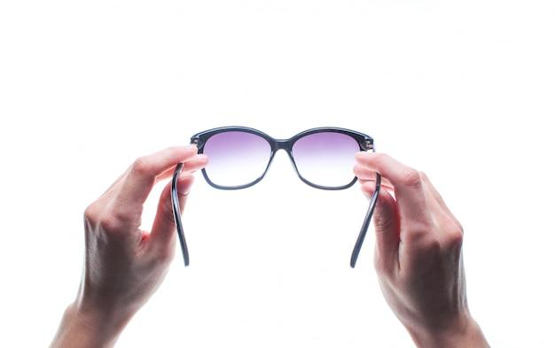 Руки держат солнцезащитные очки изолированы.