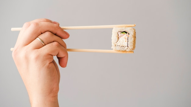 Hands holding sushi roll with chopsticks
