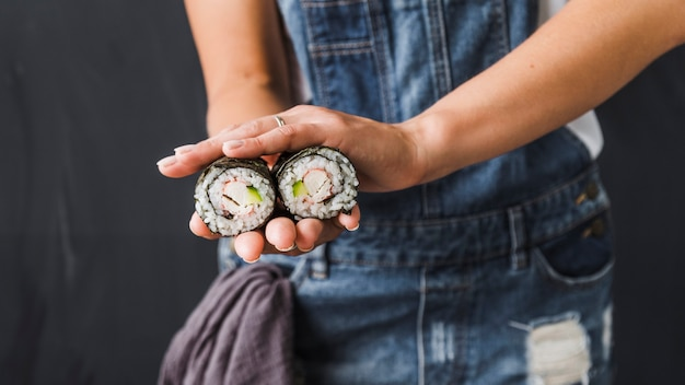 Hands holding sushi wraps