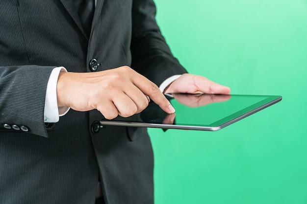 Hands holding tablet computer on light green background