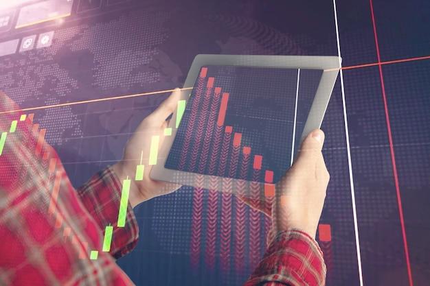 Руки держат планшет, показывая графики, идущие вниз. двойная экспозиция с графиками, цифровая. оповещение о вирусе, пандемия коронавируса, кризис, безработица. covid-19 эпидемия. обвал финансовых рынков.