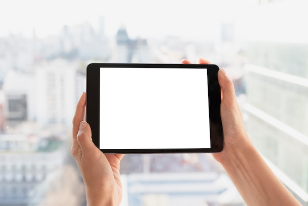 Hands holding tablet with light background
