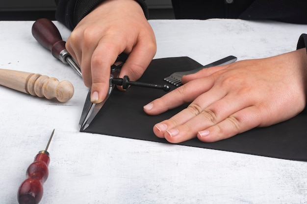 茶色の革の部分を持つタンナー ツールを持っている手