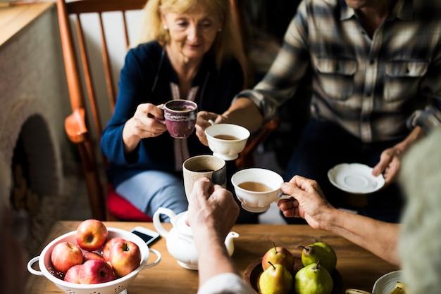 Руки, держащие чашки чая, звенящие вместе