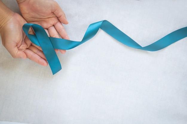 コピースペースのある白い布にティールカラーのリボンを持っている手。卵巣がんの認識、婦人科、子宮がん、外陰がん、パニック障害、心的外傷後ストレス障害(ptsd)。