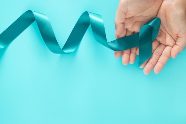 Руки держат бирюзовую ленту на фиолетовой поверхности с копией пространства