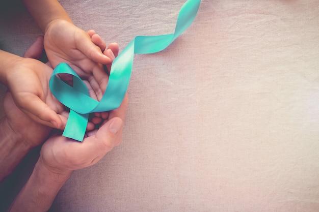 Hands holding teal ribbon, ovarian cervical cancer