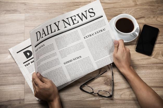 木製のテーブル、毎日新聞モックアップコンセプトにビジネス新聞を保持している手
