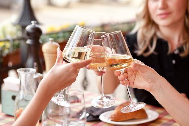 건배를 만드는 화이트 와인 잔을 들고 손. 여자 건배.
