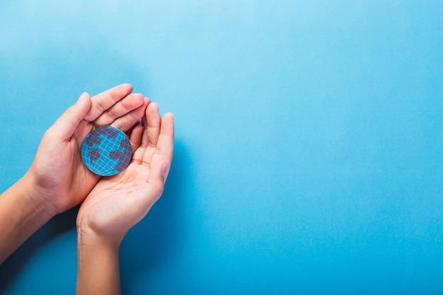 Руки держат планету земля на синем фоне - спасти мир, творческая концепция.