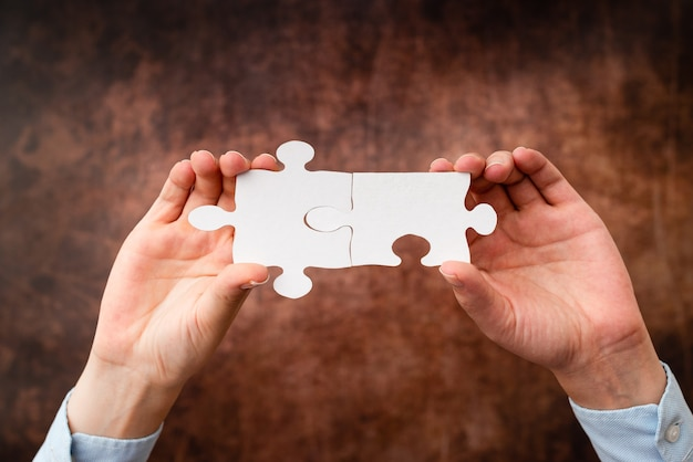 Руки, держащие две части головоломки. сотрудничество для поиска и решения отсутствующих идей на работе. бизнесмен находит стратегию для решения, соединяя мысли