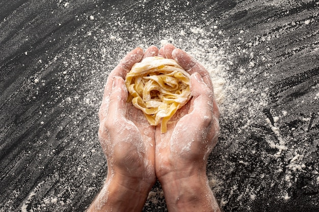 Hands holding uncooked tagliatelle