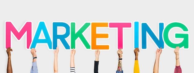 Руки, держащие красочные буквы, образующие слово маркетинг