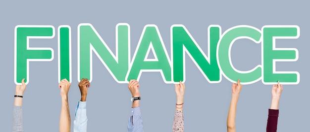 Mani che sostengono le lettere verdi che formano la finanza di parola