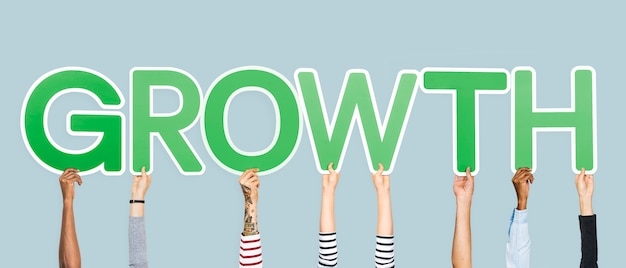Hands holding up green letters forming the word growth