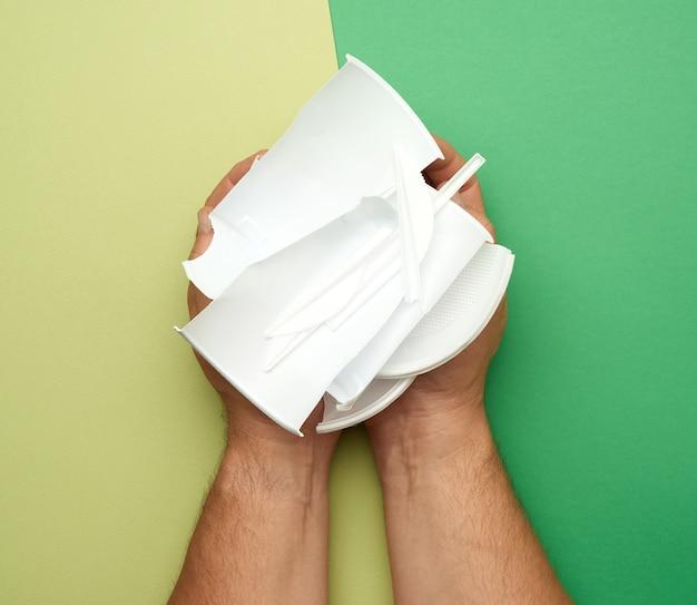 Руки, держащие использованную пластиковую посуду