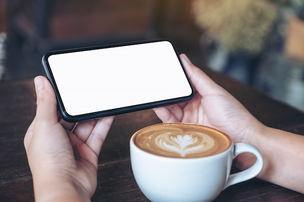 Hands holding and using a black mobile phone with blank screen horizontally for watching with coffee cup on wooden table