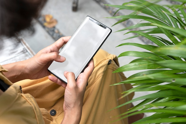 Hands holding and using mobile phone with blank screen in garden.