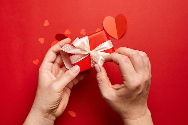 Руки держат подарочную коробку дня святого валентина на красном фоне с бумажными сердечками