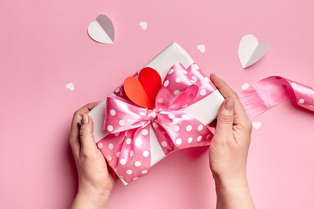 Руки держат подарочную коробку дня святого валентина с бумажными сердечками на розовом фоне