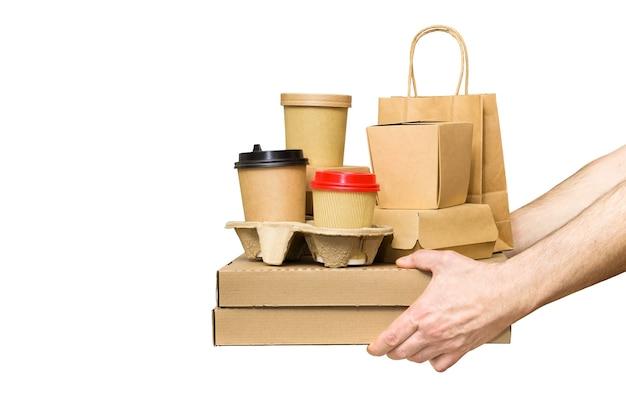 さまざまな持ち帰り用の食品容器、ピザの箱、ホルダーにコーヒーカップ、白で隔離された紙袋を持っている手。フードデリバリーサービス