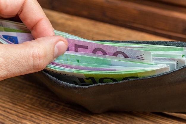 木製の背景にお金の紙幣でいっぱいの財布を持っている手