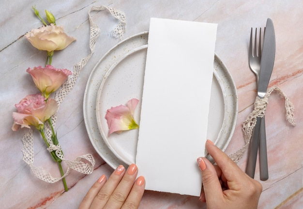 Hands holding wedding menu over a ceramic plate on a marble table decorated with flowers and ribbons
