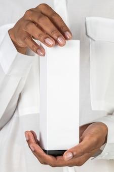 Mani che tengono una confezione cosmetica vuota bianca