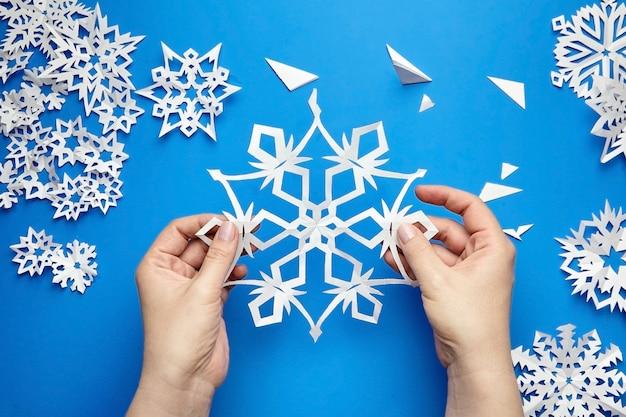 Руки держат белую вырезанную из бумаги снежинку на синей поверхности