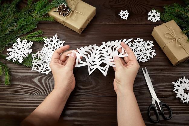 Руки держат белую вырезанную из бумаги снежинку на деревянном столе