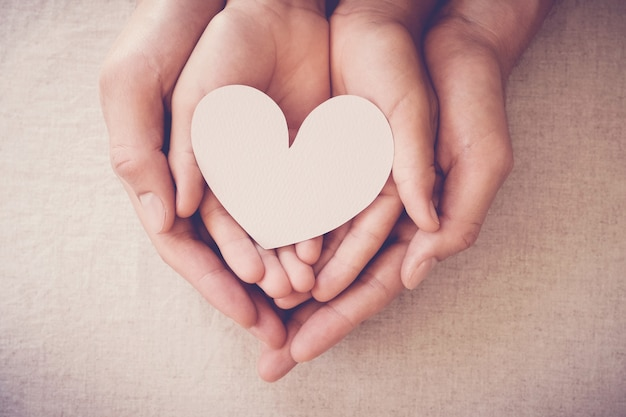 Hands holding white heart, heart health insurance, donation charity, foster child concept