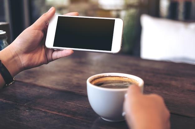 보고 게임을위한 빈 검은 스크린 흰색 휴대 전화를 들고 손