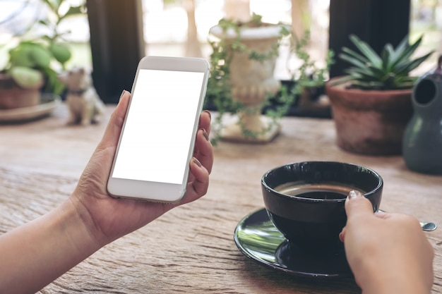 Hands holding white mobile phone with blank desktop screen and a coffee cup