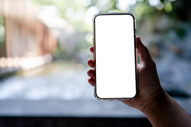 Hands holding white mobile phone with blank screen mock up, hotel spa background.
