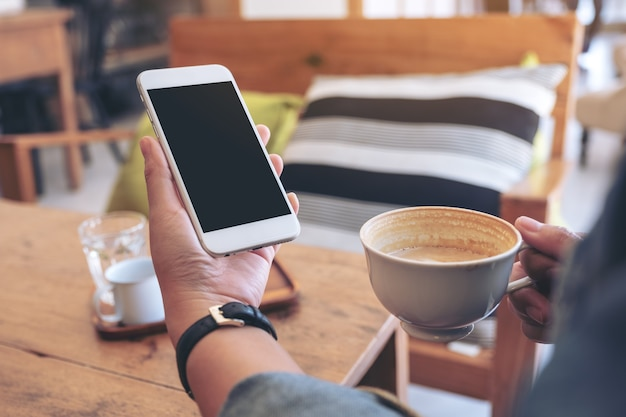 Hands holding white mobile phone with blank screen while drinking coffee in cafe